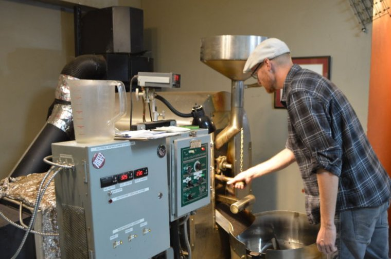 Mike Harktop checks the beans in his solar roaster.