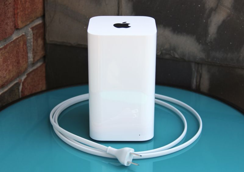 Apple's AirPort Express Wi-Fi router sitting on a blue table surrounded by its power cord.