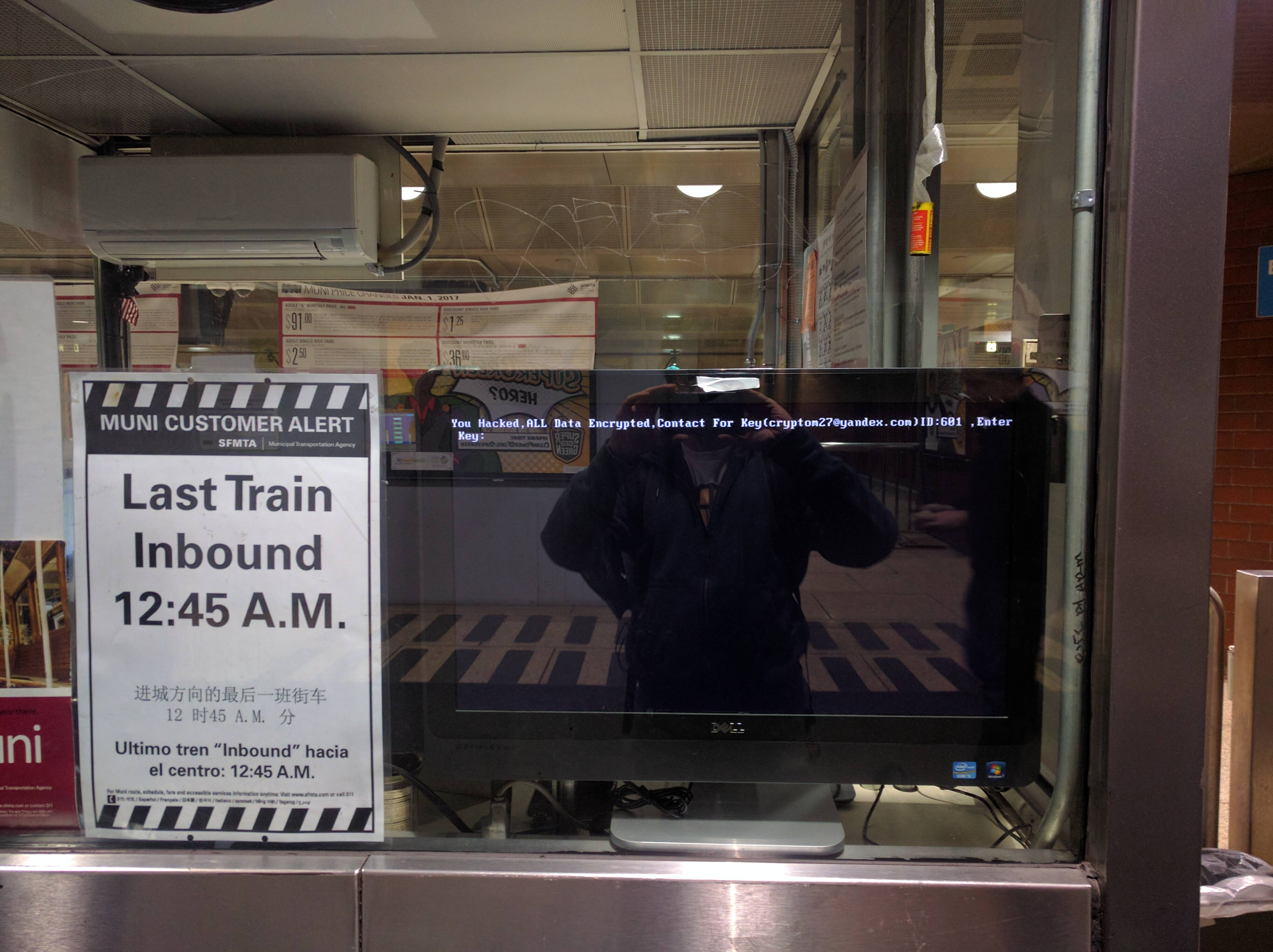 A screen at a Muni train station shows the malware message from HDDCryptor.