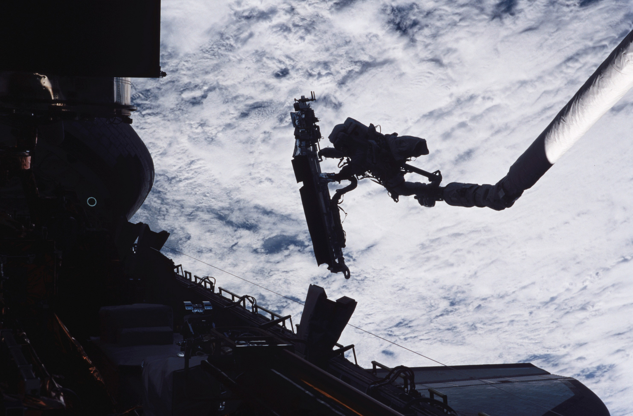 John Grunsfeld, STS-109 payload commander, is anchored on the end of the Space Shuttle Columbia's robotic arm, moving toward the giant Hubble Space Telescope in 2002.