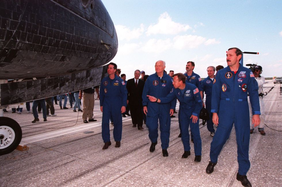 Glenn and the rest of the STS-95 crew look over <em>Discovery</em> after landing.