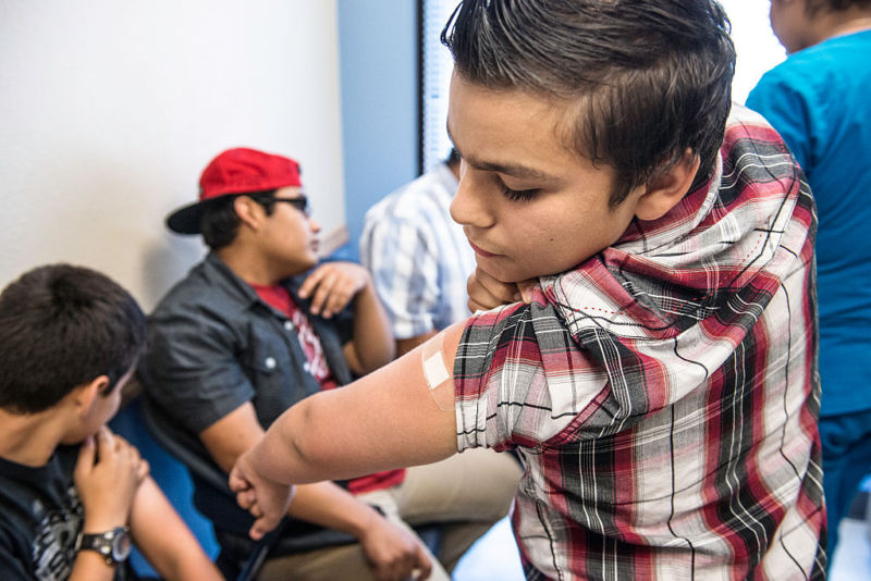 A 12-year-old boy in Texas checks his arm after receiving an HPV vaccination.
