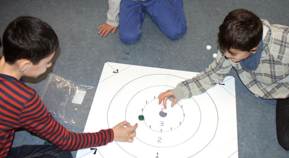 Playing crokinole on a homemade board.