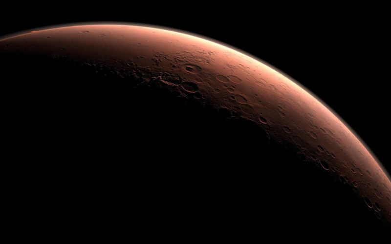 Mars at the boundary between night and day. Gale Crater is the crater with a mound inside it near the center of the image, beginning to catch morning light. Northward is to the left. This view was created using three-dimensional information from the Mars Orbiter Laser Altimeter, which flew on NASA's Mars Global Surveyor orbiter.