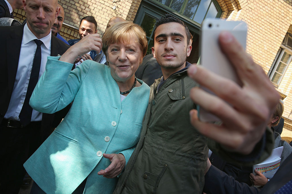 German Chancellor Angela Merkel poses for a selfie with Modamani on September 10, 2015 in Berlin, Germany. (Photo by Sean Gallup/Getty Images)