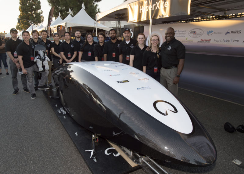 Engineering dean Gregory Washington (right) and the HyperXite crew proudly flank their entry in an early 2017 Hyperloop Pod Competition.
