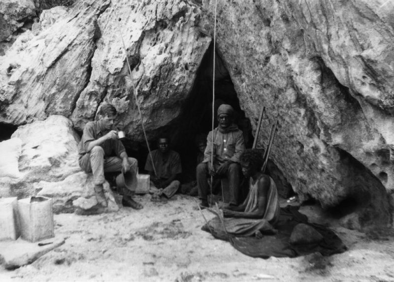Norman Tindale, pictured here in 1927 with members of a local Aboriginal group, led a mission to gather precise ethnographic and geographic data from many different Aboriginal groups. He also gathered hair from the people he interviewed, which provided DNA samples for earlier studies. The group here is at Rockshelter at Bathurst Head (Thartali) in eastern Cape York Peninsula.