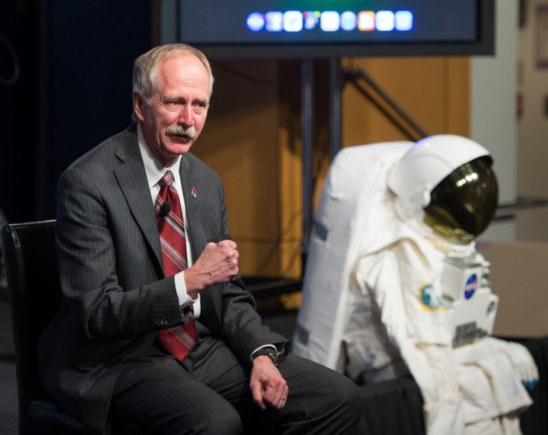 A man in a business suit stands next to a display spacesuit.