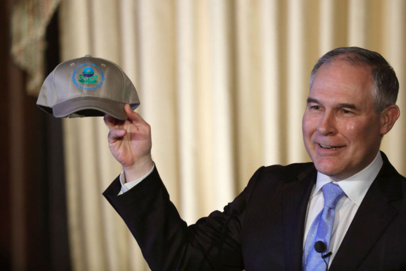 Scott Pruitt shows off a hat with the logo of the organization he now leads.