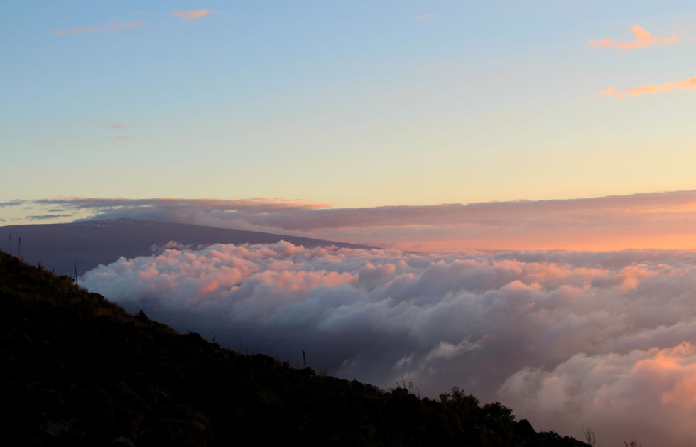 At sunset, clouds fill the valley between Mauna Kea and Mauna Loa.