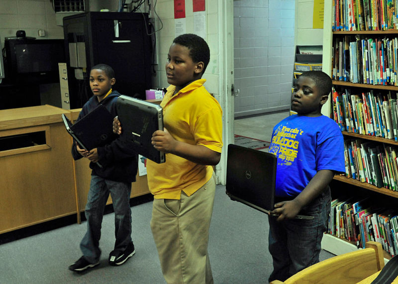 Three students—Jarquiese McCaskey, Jaquan Hawkins and Zaylan Randolph—hold computers as they enter the school library where they will attempt to do work on laptops with very limited Internet access. As testing time for students is ongoing this time of year, students at Monroe Intermediate School in Lower Peach Tree, Alabama are at a disadvantage as Internet capabilities at the school are limited.