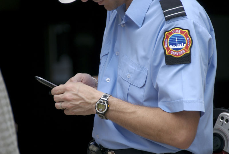 Fire marshal texting a message on his cell phone.