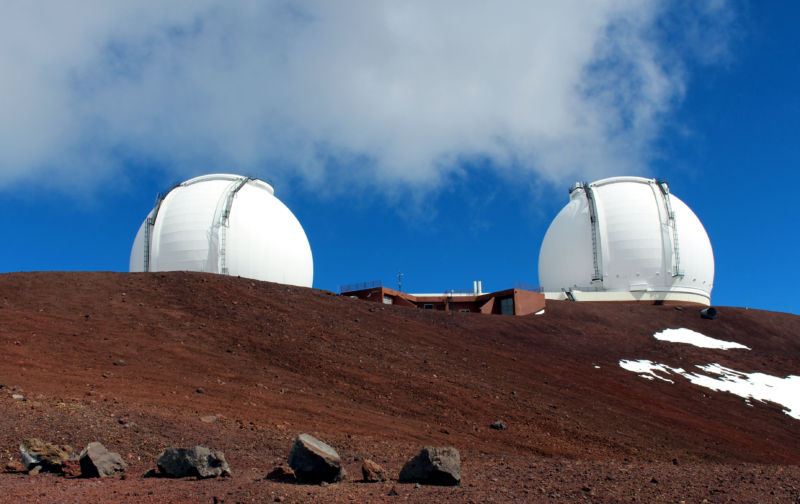 Two large white domes on a barren reddish landscape.