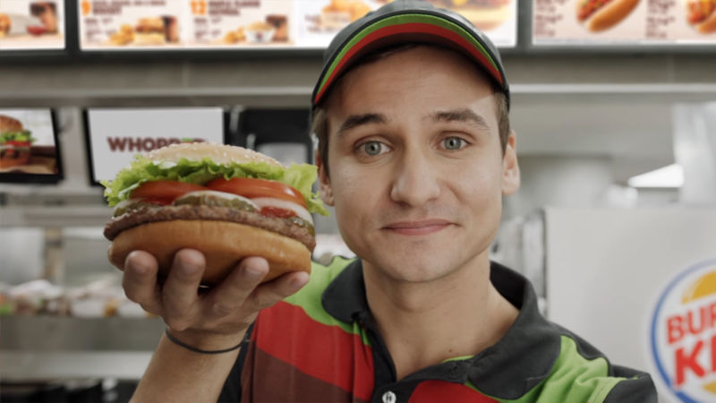 An actor on a soundstage holding an exaggerated facsimile of a Burger King product.
