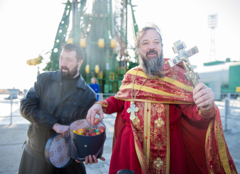 An Orthodox priest hands out Easter eggs to the media at the Baikonur Cosmodrome launch pad after blessing the Soyuz rocket on Wednesday, April 19, 2017 in Kazakhstan.