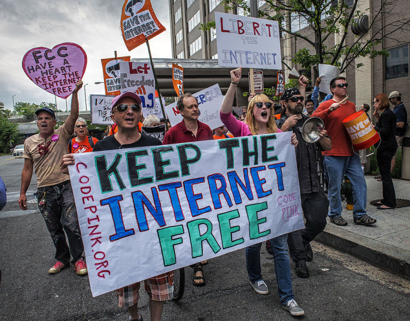 Net neutrality supporters march past the FCC headquarters before a commission meeting on May 15, 2014.