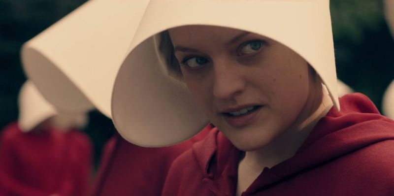 The handmaid June (Elizabeth Moss) must wear regulation red, with a bonnet covering her face, to signify her role as a slave designated to bear children for a prominent man.