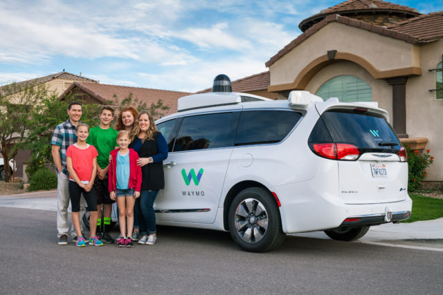 One of the earliest families in Waymo's public trial in Phoenix poses with a Waymo minivan.