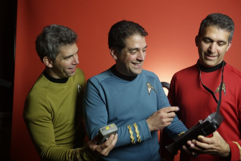 Harris brothers pose in uniform with prop tricorders from the <em>Star Trek</em> series.