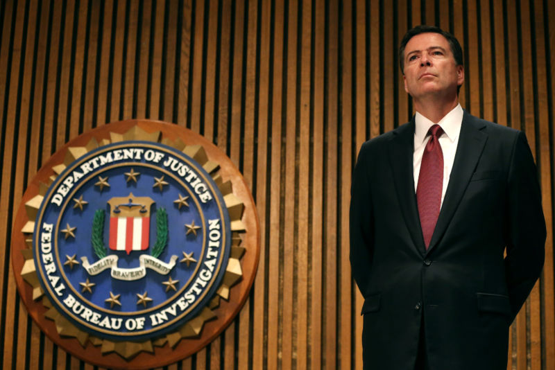Then-FBI Director James Comey stands in front of a FBI wall sign.
