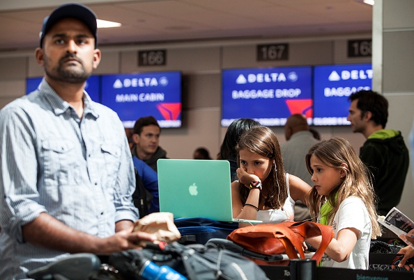 Kids watch a laptop screen at Pearson International airport in Toronto