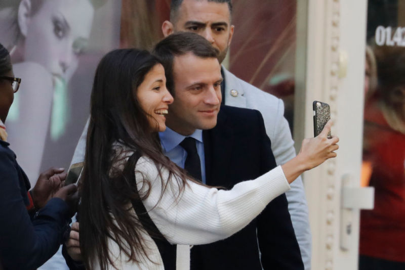 Newly elected French president Emmanuel Macron poses with a woman for a selfie.