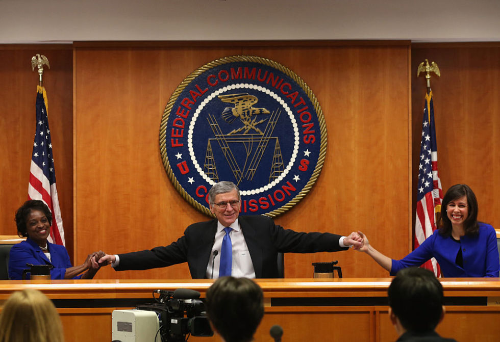Then-FCC Chairman Tom Wheeler celebrates with fellow Democratic commissioners Mignon Clyburn (L) and Jessica Rosenworcel (R) after the February 2015 net neutrality vote.