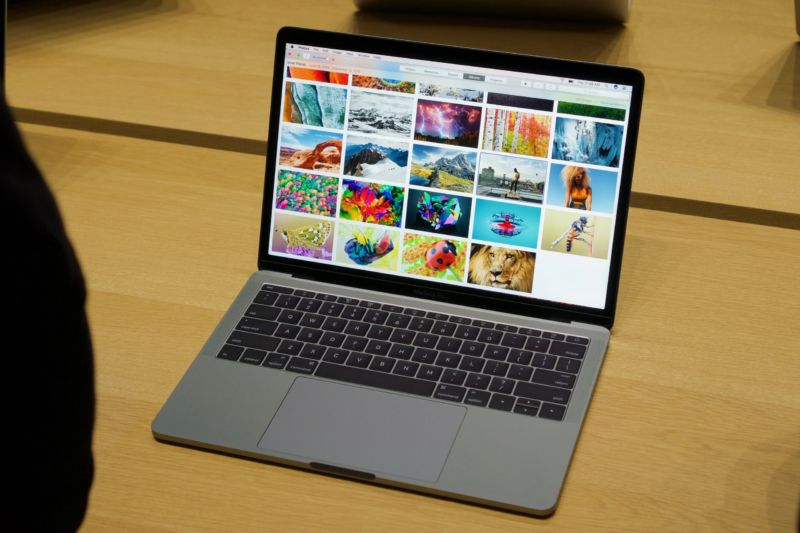 MacBook Pro without TouchBar, sitting on a wooden table, showing photos on its screen.