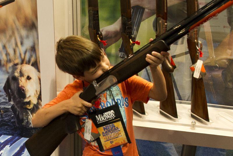 A boy under his parents' supervision aims a shotgun.