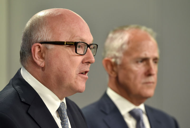 Australia's Attorney General George Brandis (L) speaks at a press conference Australia's Prime Minister Malcolm Turnbull looks on in Sydney on December 30, 2015.