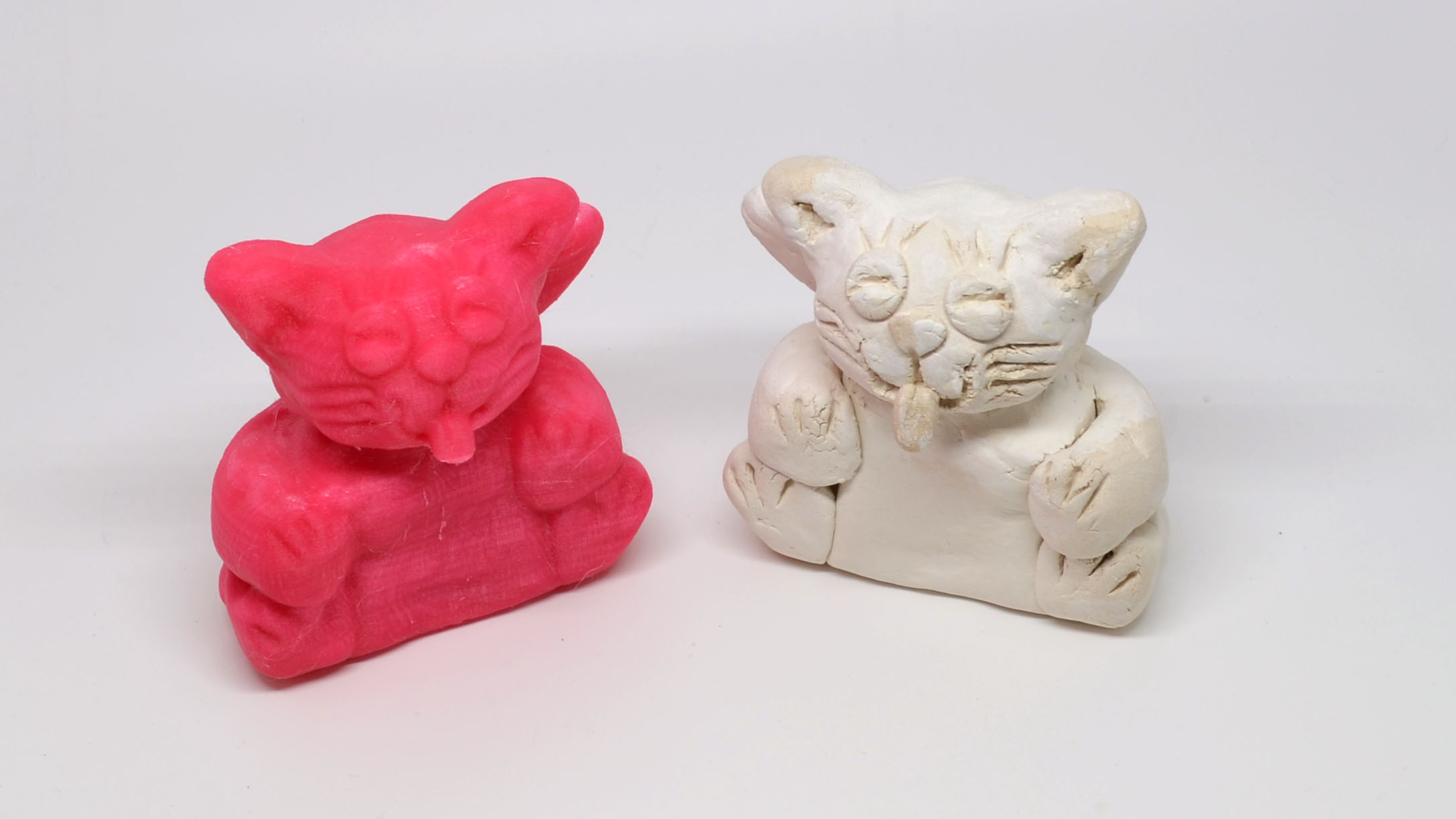 The final model (left) printed in PLA on the MOD-t. The Matter and Form 3D Scanner produced the closest reproduction of the original clay cat model (right) out of any of the solutions in this roundup.