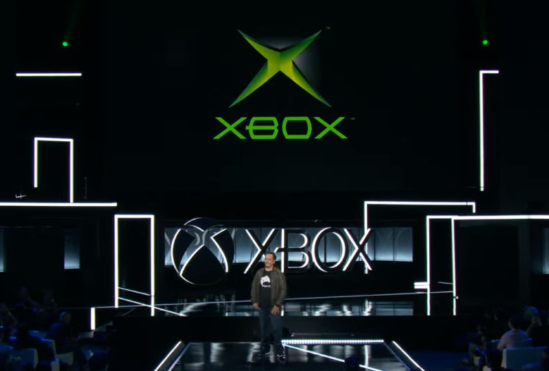 "Phil Spencer literally stands next to two Xbox ""one"" logos."