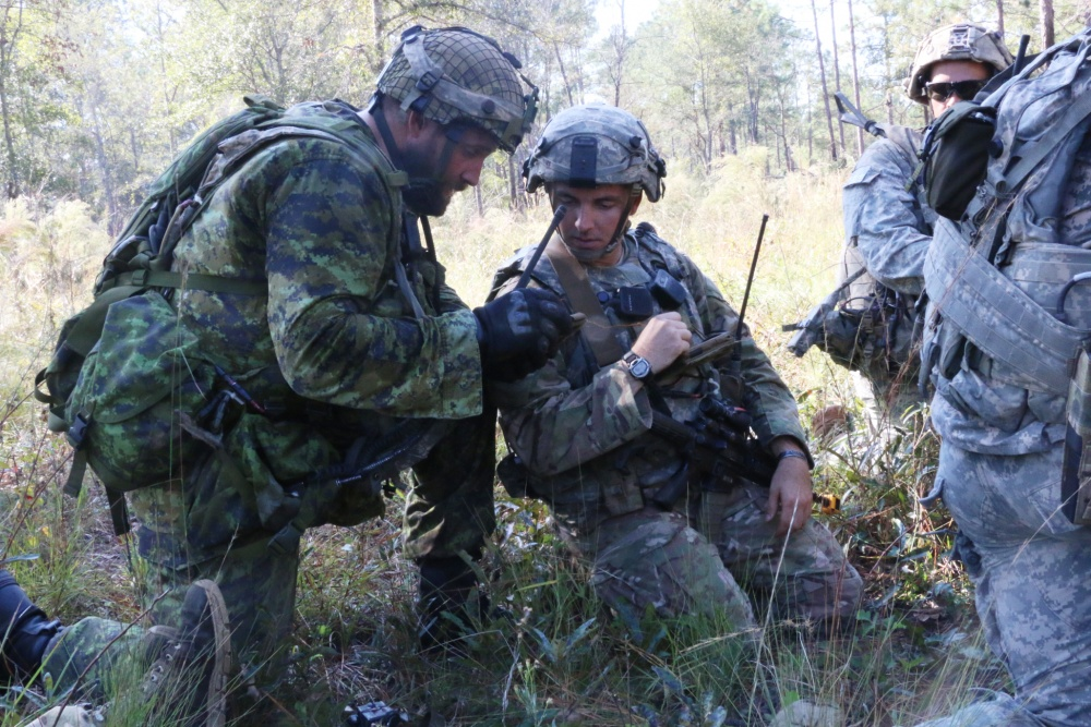 Canadian Armed Forces Master Corporal James Dowson (left), a section leader with the Lake Superior Scottish Regiment, and US Army 1st Lt. Travis Hines, a platoon leader with Alpha Company, 3rd Battalion, 7th Infantry Regiment, 2nd Infantry Brigade Combat Team, 3rd Infantry Division, plan their next movement during Bold Quest at Fort Stewart, Georgia, October 31, 2016.