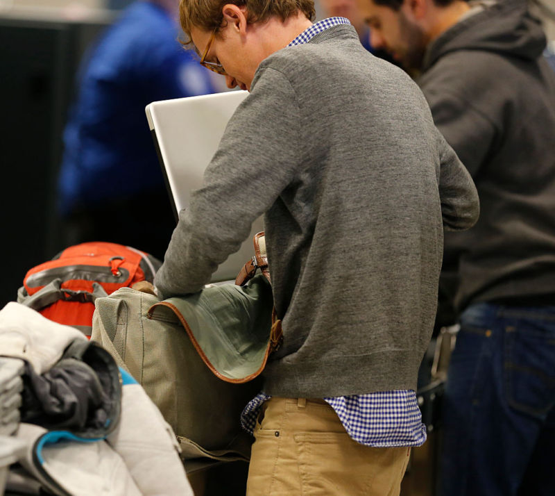 A passenger places a laptop computer back into his bag after passing through a TSA check point at Salt Lake City International Airport.