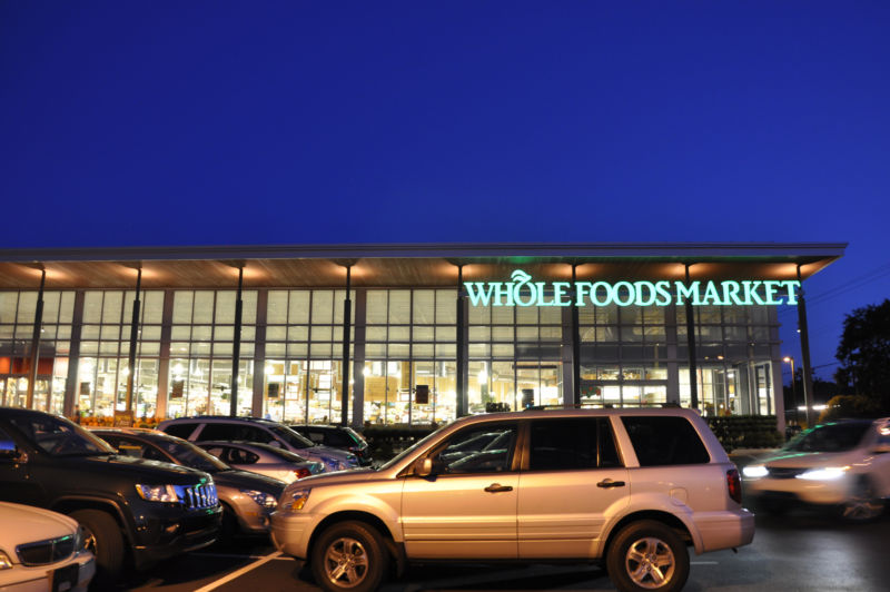 The outside of a Whole Foods Market store at night, with the store signage lit up in green.