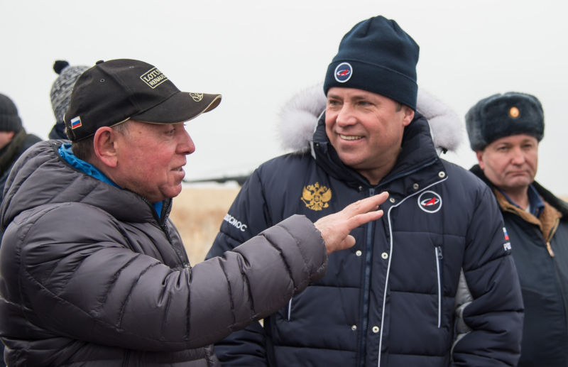 The head of Roscosmos, Igor Komarov (right), talks to former cosmonaut Alexander Volkov.