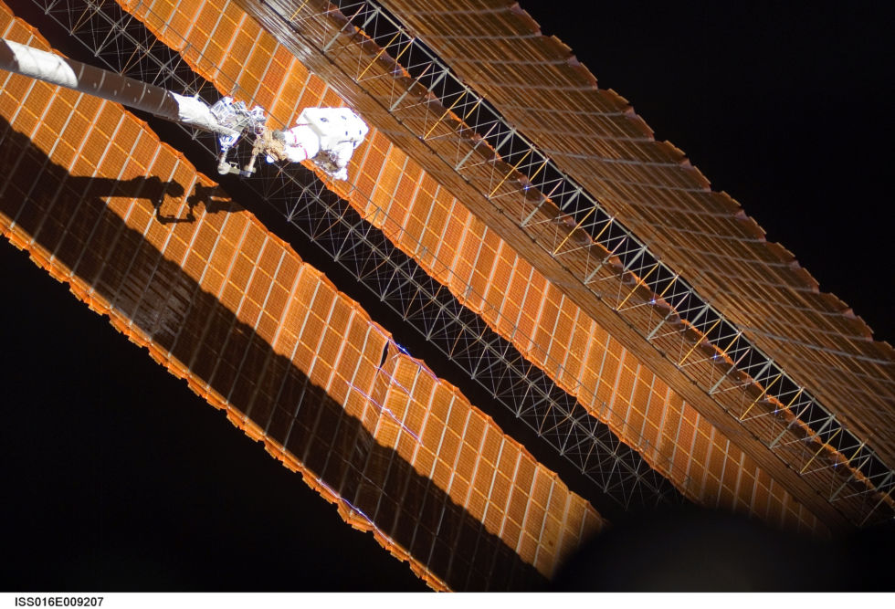 While anchored to a foot restraint on the end of the Orbiter Boom Sensor System, Parazynski assesses his improvised fix to the solar array.