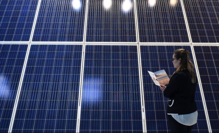 A young woman looks at a photovoltaic installation at a booth at the InterSolar Europe trade fair in the southern German city of Munich on June 1, 2017.