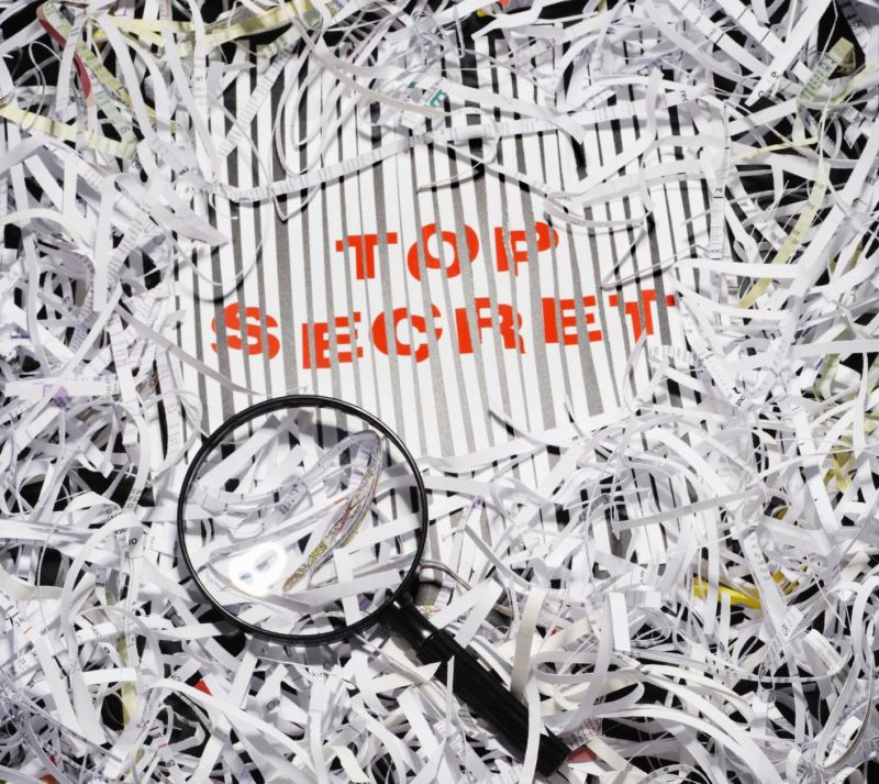Shredded documents with a magnifying glass and the words,