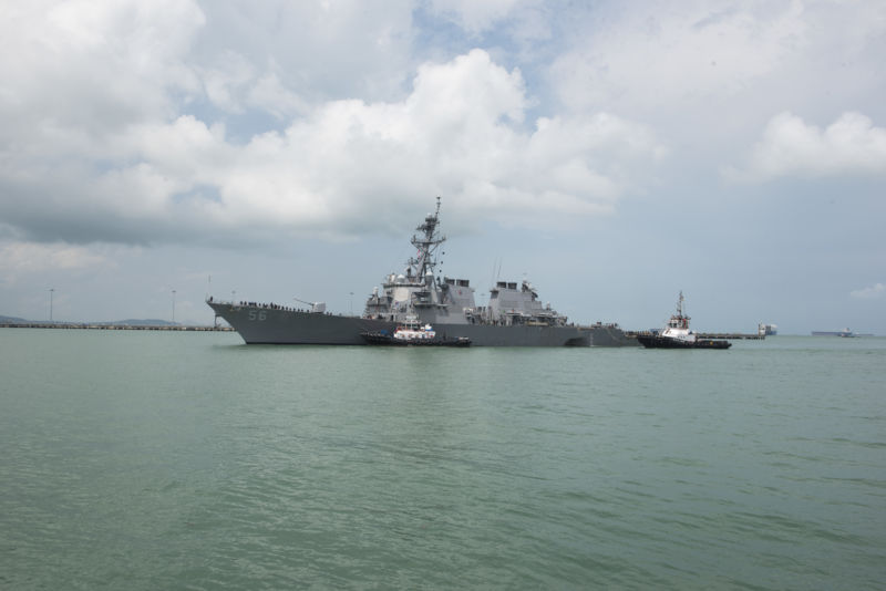 Tugboats from Singapore assist the guided-missile destroyer USS <em>John S. McCain</em> (DDG 56) as it steers toward Changi Naval Base, Republic of Singapore, following a collision with the merchant vessel <em>Alnic MC</em> while underway east of the Straits of Malacca and Singapore on August 21. Ten sailors died in the collision.