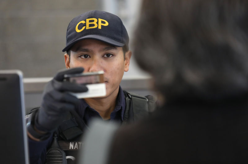 A US Customs and Border Protection officer checks identifications as people cross into the United States from Mexico on September 23, 2016 in San Ysidro, California.