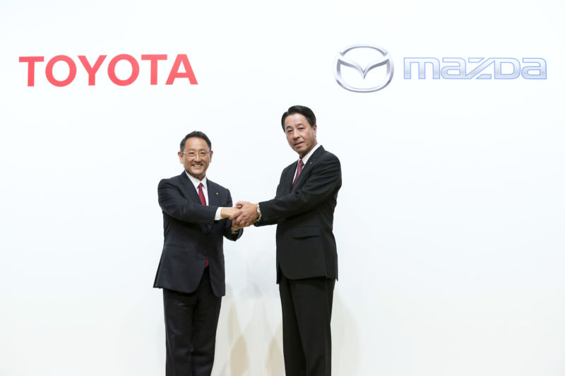 Toyota President Akio Toyoda, left, and Mazda President and CEO Masamichi Kogai, right, shake hands during a photo session at a joint press conference on August 4, 2017 in Tokyo, Japan.