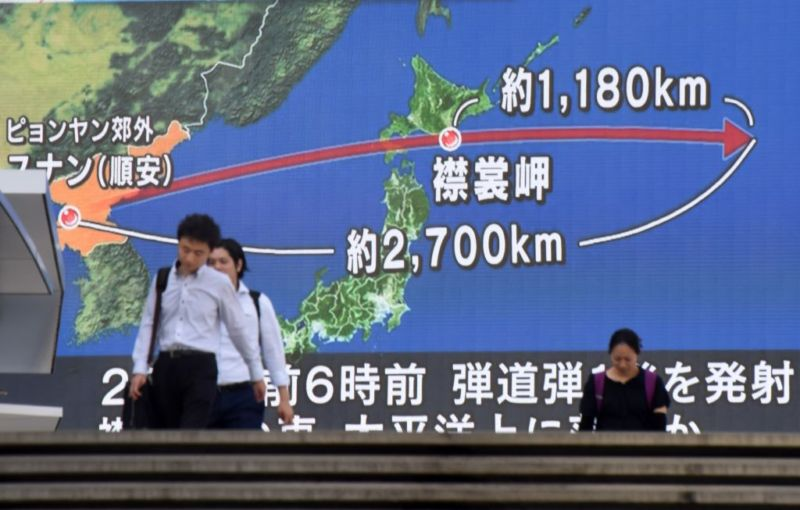 enlarge pedestrians walk in front of a huge screen displaying a map of an r and the korean peninsula in tokyo on august 29 2017 following a north