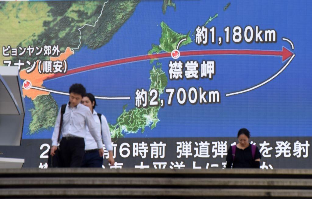 Enlarge Pedestrians Walk In Front Of A Huge Screen Displaying A Map Of Japan R And The Korean Peninsula In Tokyo On August 29 2017 Following A North