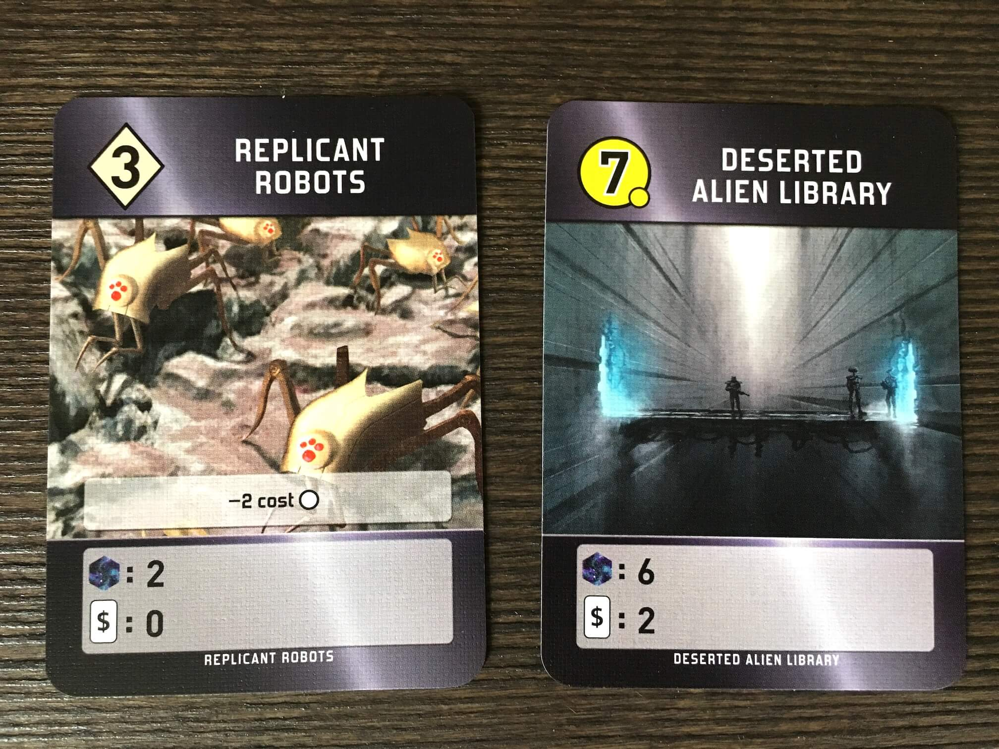 A development (left) and a world (right). At the bottom of the cards, you can see that Replicant Robots produces 2 points and no cards per round, while the (expensive) Deserted Alien Library produces 6 points and 2 cards per round. The Robots' special ability makes subsequently played worlds cheaper.
