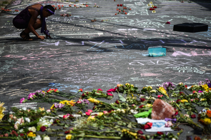CHARLOTTESVILLE, VIRGINIA—A woman leaves a note on the ground as  people gather at a memorial for Heather Heyer after her funeral service on Wednesday. Heyer was killed after a car rammed into a group of people during a planned Unite the Right rally on August 12. The Daily Stormer's celebration of the death sparked a backlash.