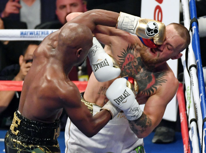 Floyd Mayweather Jr. (L) hits Conor McGregor in the sixth round of their super welterweight boxing match at T-Mobile Arena on August 26, 2017 in Las Vegas, Nevada. Mayweather won by 10th-round TKO.