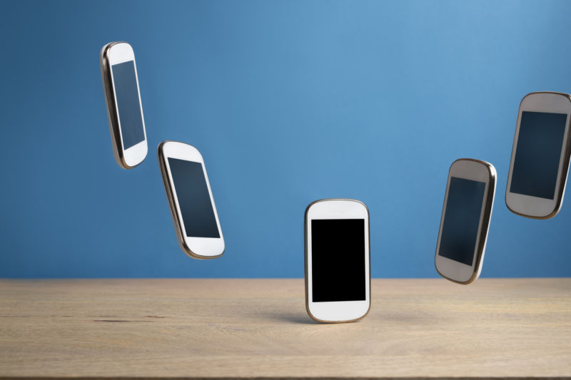 An illustration of several smartphones hovering above a table.
