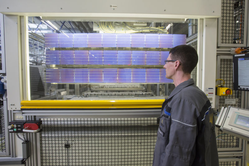 An employee inspects photovoltaic cells following electrical contact soldering during manufacture at Solarworld AG in Freiberg, Germany, in July 2016.