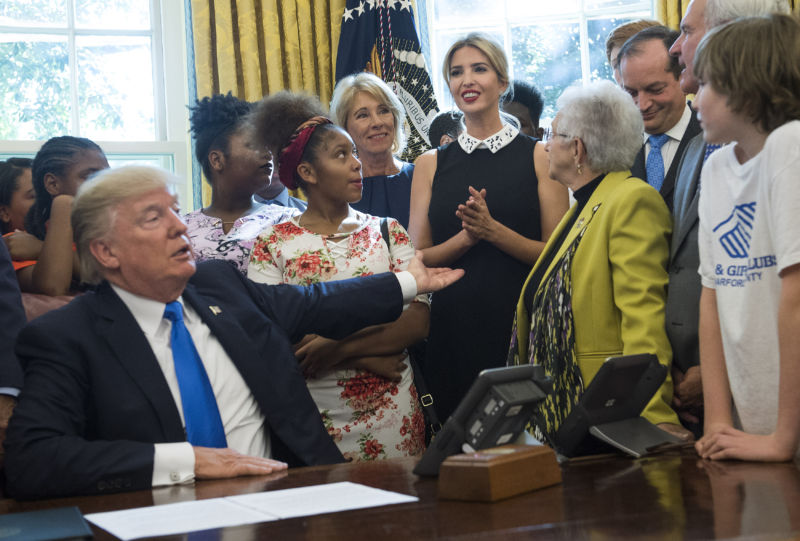President Donald Trump motions to his daughter Ivanka Trump as she delivers remarks alongside students and members of Congress and her father's administration, before President Trump signed a memorandum to expand access to STEM (science, technology, engineering, and math) education in the Oval Office at the White House on September 25, 2017 in Washington, DC.